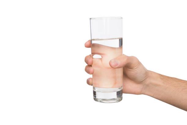 白で隔離水のガラスを持っている男性の手 ストックフォト