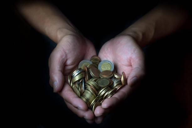 männliche hand mit goldenen münzen. sparen, geld, finanzen spende, geben und bussiness-konzept. schwarzer hintergrund. herzform. - spenden sammeln stock-fotos und bilder