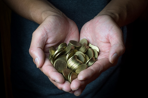 istock Male hand holding golden coins. Saving, money, finance donation, giving and bussiness concept. Black background. Heart shape. 869226494