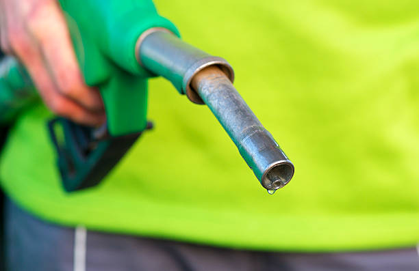 Male hand holding green pump Male hand holding green pump biodiesel stock pictures, royalty-free photos & images