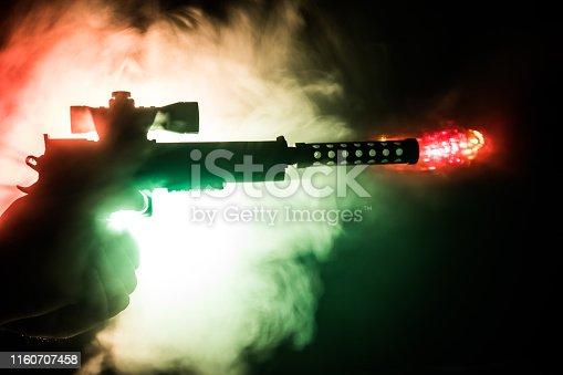 Male hand holding gun on black background with smoke toned back lights. Silhouette of a gun in hand. Crime concept. Selective focus