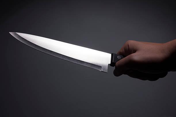 male hand holding large, sharp, shiny kitchen knife - große waffen stock-fotos und bilder