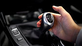 Male hand holding manual gearbox in car, test drive of new automobile, closeup