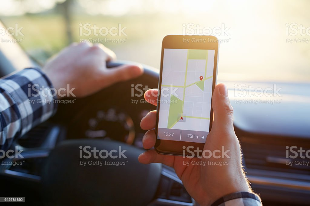 Male hand holding mobile phone with gps map bildbanksfoto