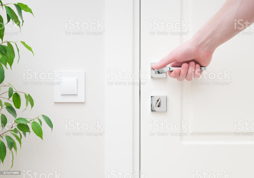 Male hand holding modern door handle. Close-up elements of the interior of the apartment stock photo