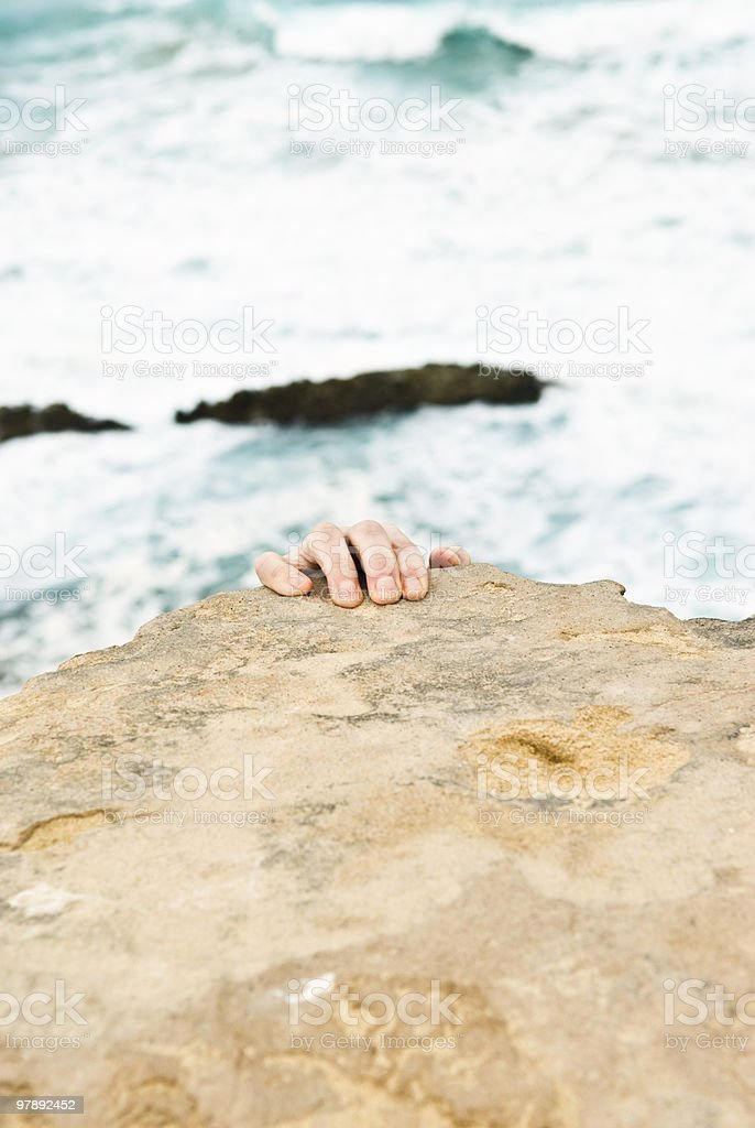 Male hand holding on to cliff`s edge. royalty-free stock photo