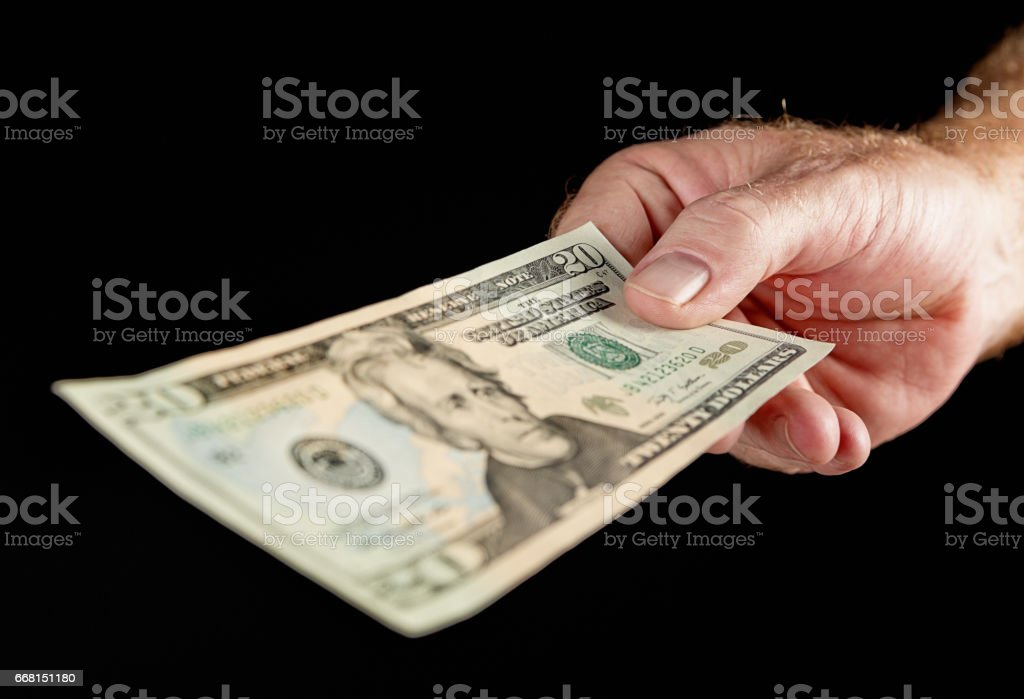 Male hand holding out American Twenty Dollar banknote stock photo