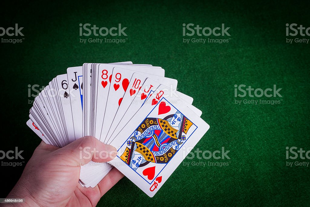 Male hand holding pack of cards on green felt background stock photo