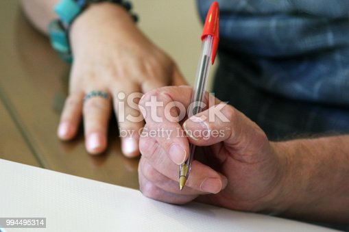 Man´s hand holding a pen in the foreground, and out of focus female hand in the background