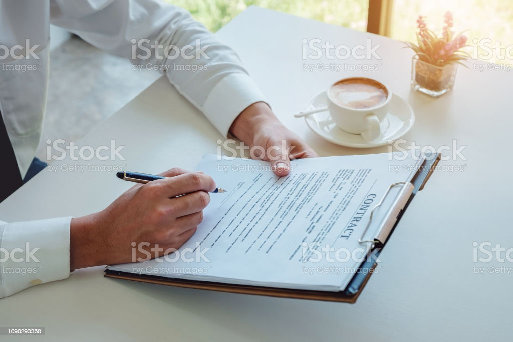 male hand holding pen to signature Contract application for Signing...