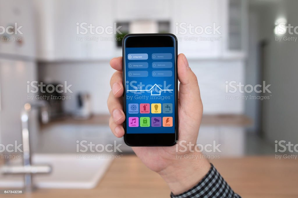 male hand holding phone with app smart home kitchen house stock photo