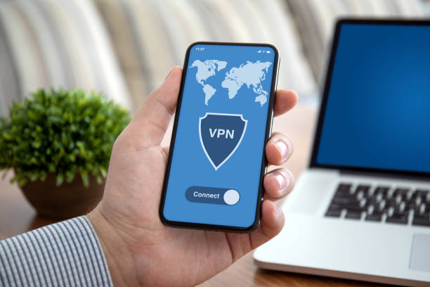 male hand holding phone with app vpn over table laptop male hand holding phone with app vpn on the screen over table with laptop in the office vpn stock pictures, royalty-free photos & images