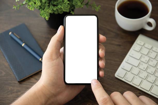 männliche Hand halten Telefon mit isoliertem Bildschirm im Büro – Foto