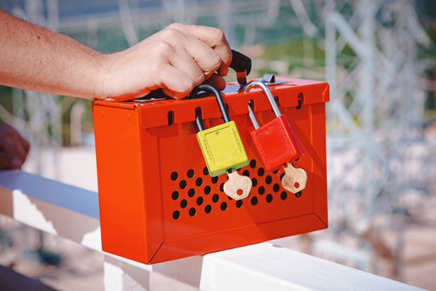 male hand holding red safe lockout/tagout box Detail of worker man hand holding red safety box lock box ensures for safe lockout tagout solutions front of power plant station outdoor lockout stock pictures, royalty-free photos & images