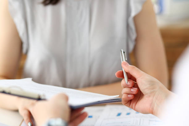 Male hand holding silver pen offering some papers for approval terms of cooperation pact stock photo
