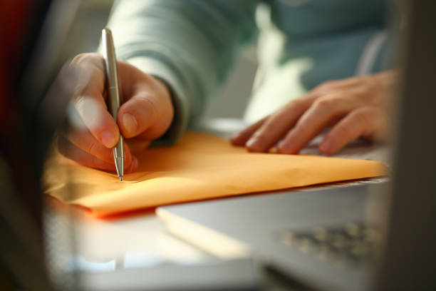 Male hand holding silver pen Male hand holding silver pen. Fill in address on yellow envelope of mail correspondence for application hiring concept sending stock pictures, royalty-free photos & images
