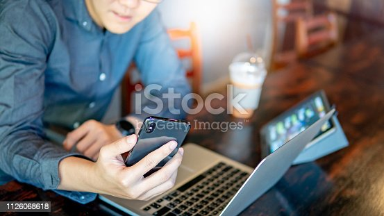1016971522 istock photo Male hand holding smartphone. Businessman using laptop computer and digital tablet while working in the cafe. Mobile app or internet of things concepts. Modern lifestyle in digital age. 1126068618