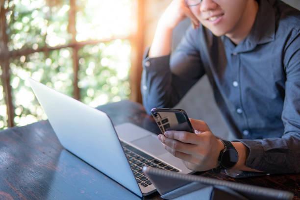 Männliche Hand Holding Smartphone. Geschäftsmann mit Laptop-Computer und digital-Tablette während der Arbeit im Café. Mobile app oder Internet der Dinge-Konzepte. Moderner Lifestyle im digitalen Zeitalter. – Foto