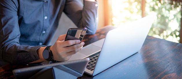 istock Male hand holding smartphone. Businessman using laptop computer and digital tablet while working in the cafe. Mobile app or internet of things concepts. Modern lifestyle in digital age. 1130938108