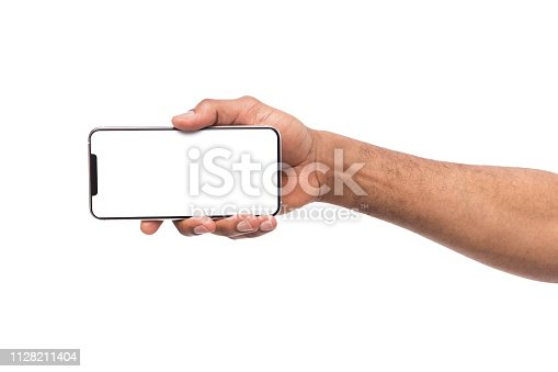 istock Male hand holding smartphone in horizontal orientation 1128211404