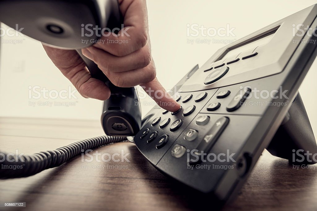 Male hand holding telephone receiver and dialing a phone number stock photo