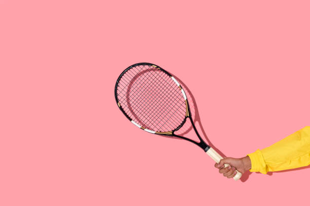 male hand holding tennis racket on pink background stock photo