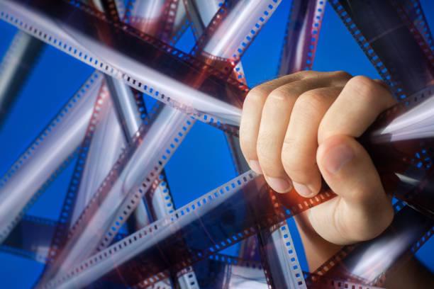 männliche hand hält der film. verbraucher-inhalte. neon-beleuchtung. - medium strähnchen stock-fotos und bilder