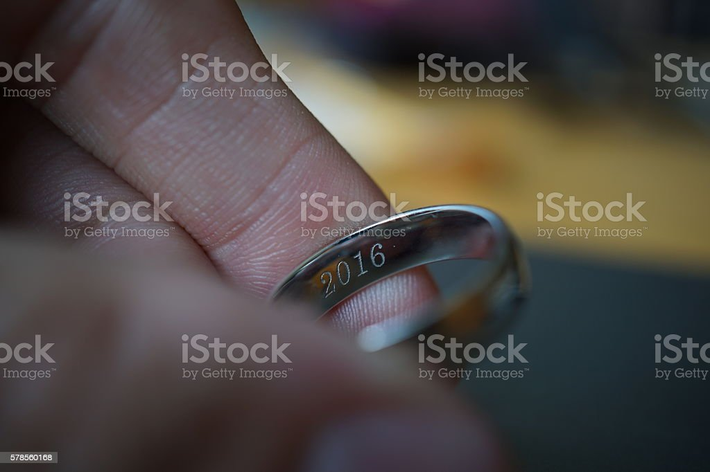 Male hand holding wedding ring with an engraved year 2016 stock photo