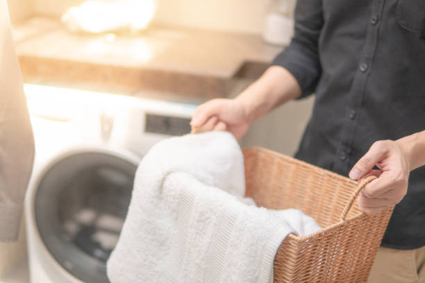 male hand holding wooden laundry basket with white towel inside near washing machine in laundry room. home living concept - laundry laundry room stock pictures, royalty-free photos & images
