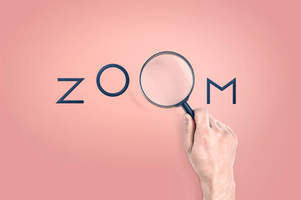Male hand holds a large magnifying glass which serves as a letter in a word ZOOM. Male hand holds a large magnifying glass which serves as a letter in a word ZOOM. Seeing details. Zooming in. Concentration and effort. zoom effect stock pictures, royalty-free photos & images