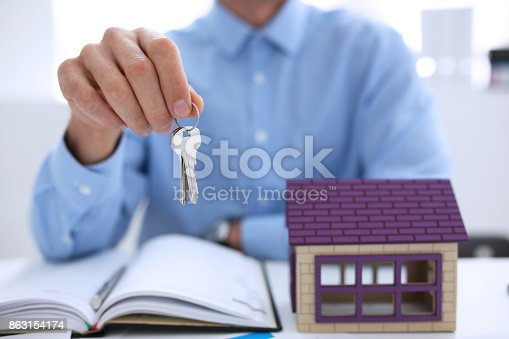 istock Male hand holds the key to the lock in the hand against the backdrop 863154174