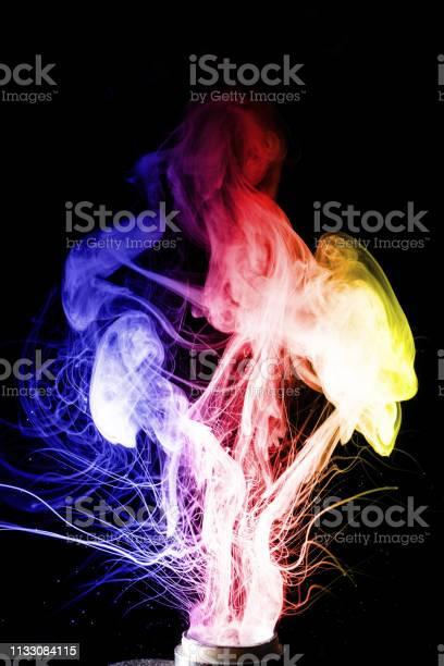 Man Hand Houdt Vape Vape Wolken Splash Van Coil Op Zwarte Achtergrond Mist Is Blauw Rood En Gele Kleuren Voorraad Geïsoleerde Rook Met Spray Kokend Glycerine Stockfoto en meer beelden van Abstract