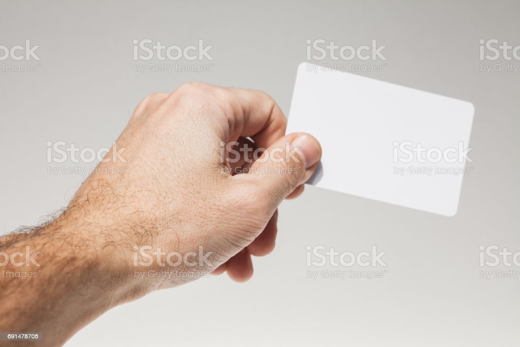 Male hand holds white empty card over gray stock photo