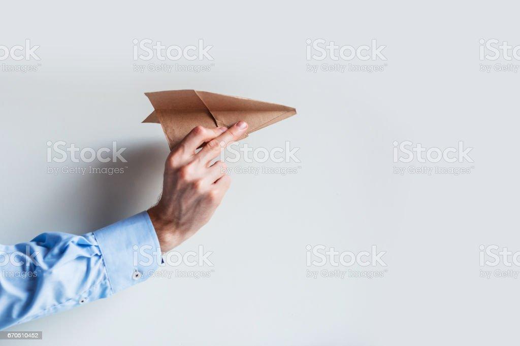 Une main masculine dans un uniforme de la chemise bleue lance un avion en papier. - Photo