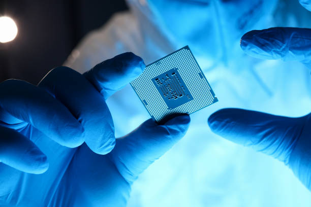 Male hand in blue protective gloves hold micro rocessor closeup Male hand in blue protective gloves hold micro rocessor closeup. Protecting flash memory storage media information security concept computer chip stock pictures, royalty-free photos & images