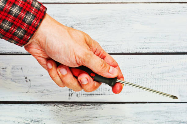 Male hand in checkered shirt holding a screwdriver stock photo