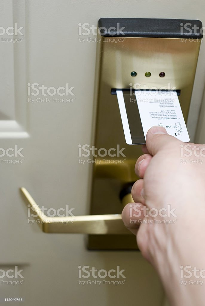 Male Hand Inserting Card Key into Electronic Hotel Door Lock royalty-free stock photo