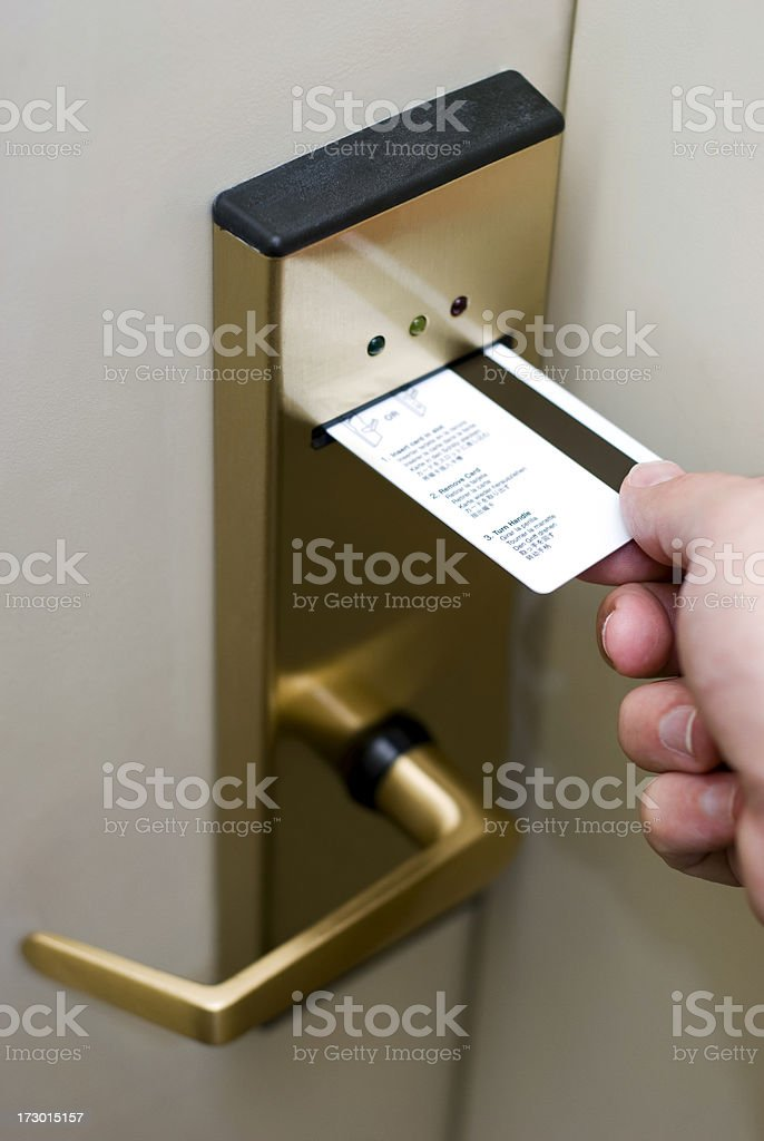 Male Hand Inserting Card Key into Electronic Hotel Door Lock stock photo
