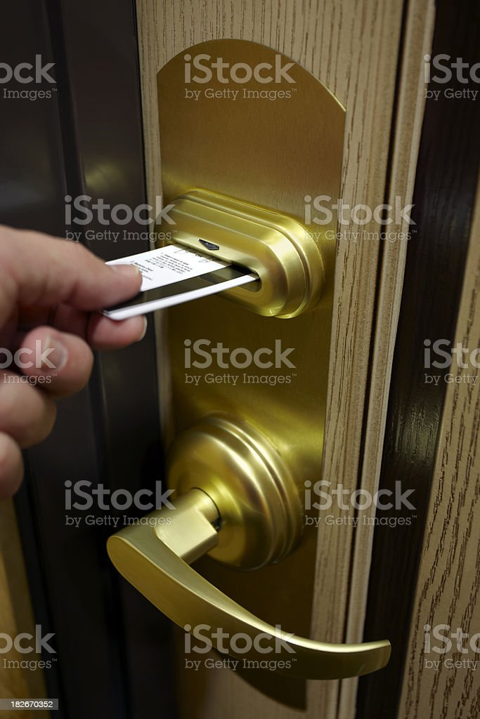 Male Hand Inserting Key Card Into Hotel Room Door Lock stock photo