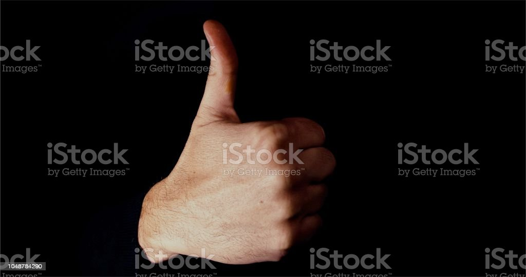 Male hand making a big thumbs up sign, Emotionally lit on black background stock photo