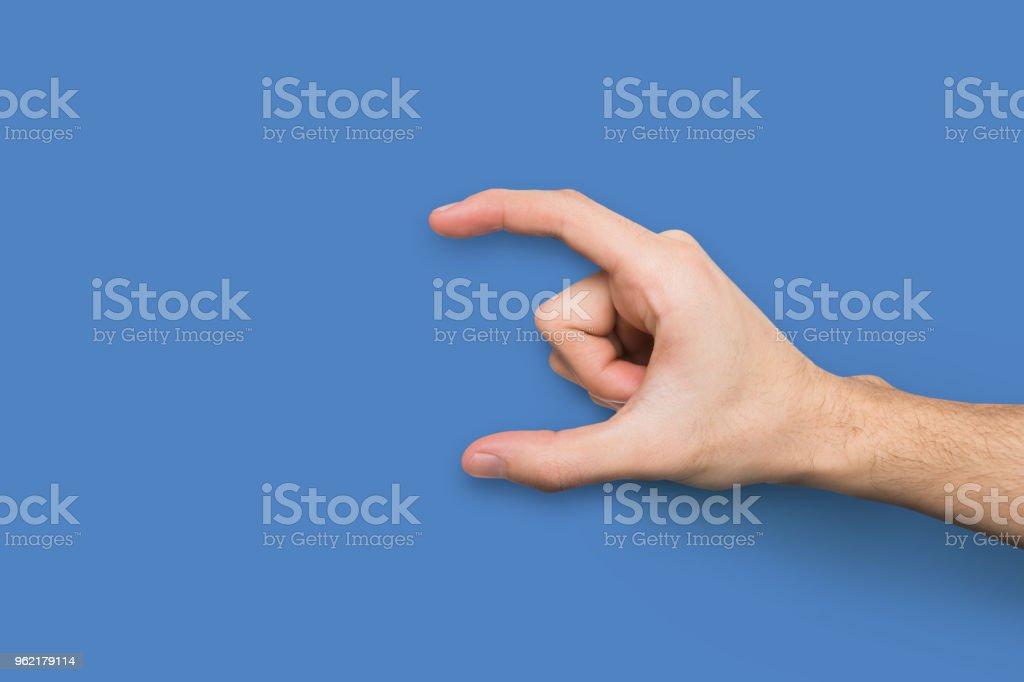Macho mano medir algo en el fondo azul - Foto de stock de Actividad móvil general libre de derechos