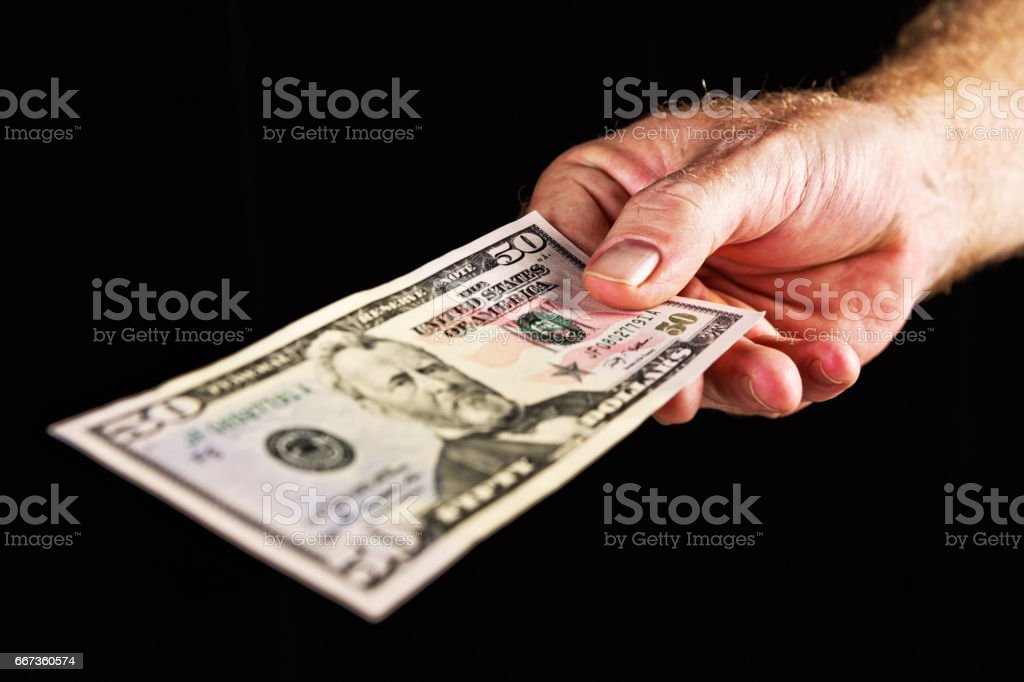 Male hand offers US fifty dollar banknote against black stock photo