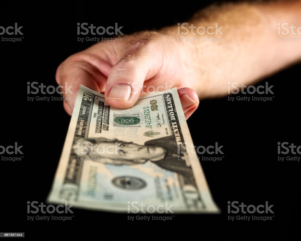 Male hand offers US twenty dollar banknote against black stock photo