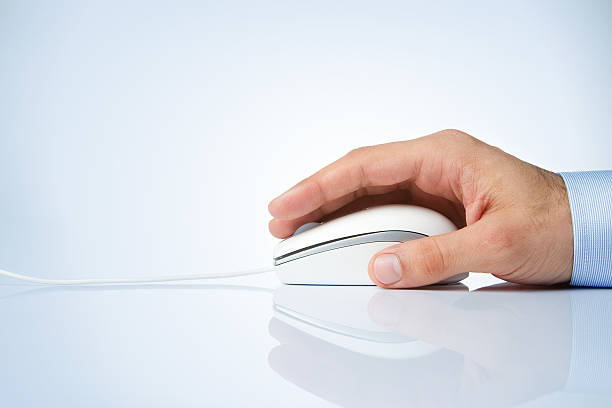 a male hand on a computer mouse on white background - computer mouse stock photos and pictures