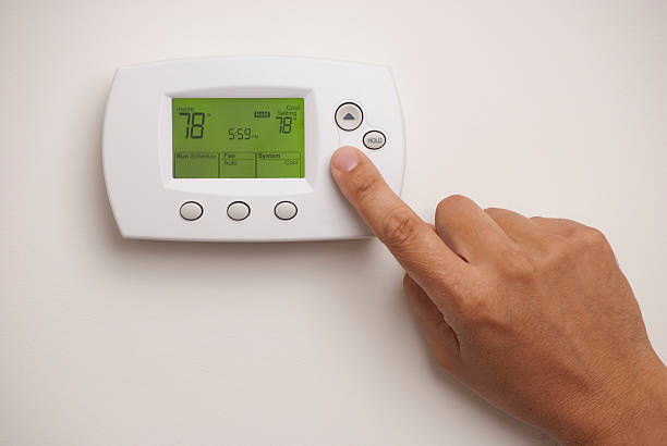 male hand on digital thermostat set at 78 degrees - ayarlamak stok fotoğraflar ve resimler