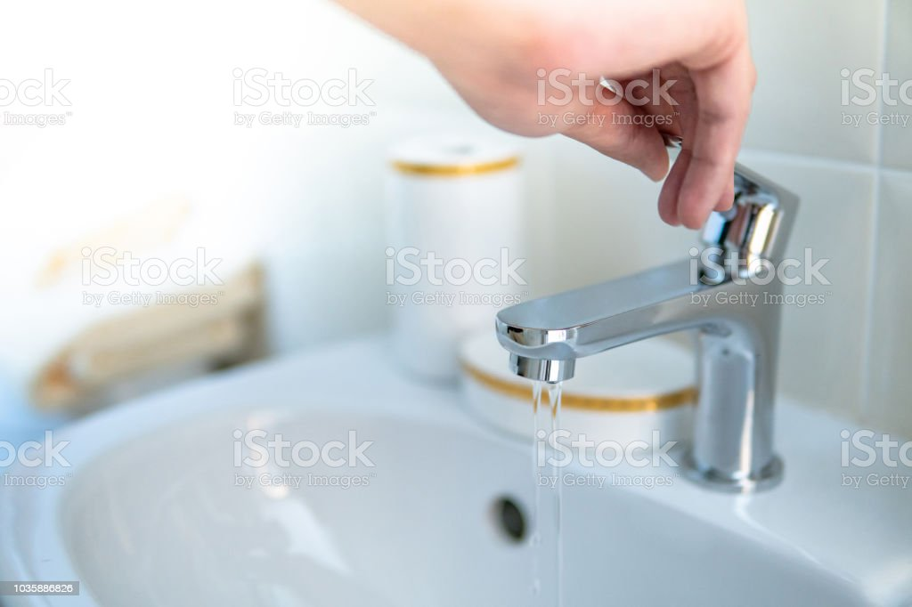 Male hand opening water tap or faucet in bathroom. Save water at home...