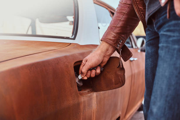 hanens hand öppnar gas locket på en trimmad retro bil för tankning. - stay tuned bildbanksfoton och bilder