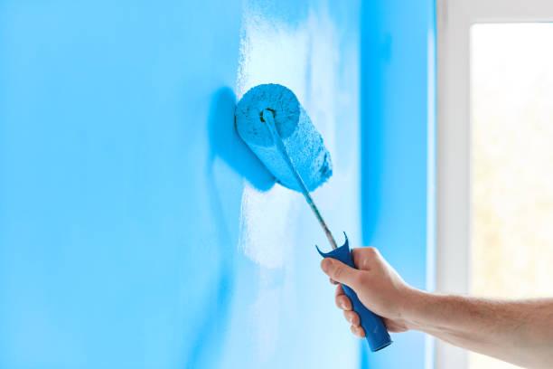 мужская ручная роспись стены с краской ролика. картина квартиры, ремонт с синей краской цвета - краска стоковые фото и изображения