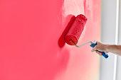 男性の手絵画壁ペイント ローラー。ピンク色のペンキで改修塗装アパート
