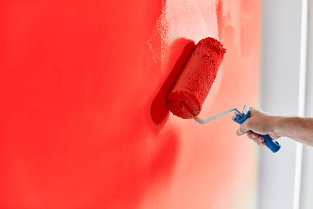 Male hand painting wall with paint roller. Painting apartment, renovating with red color paint stock photo